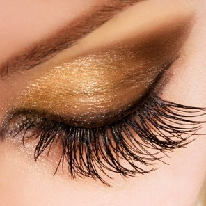 Woman eye with extremely long eyelashes and golden makeup